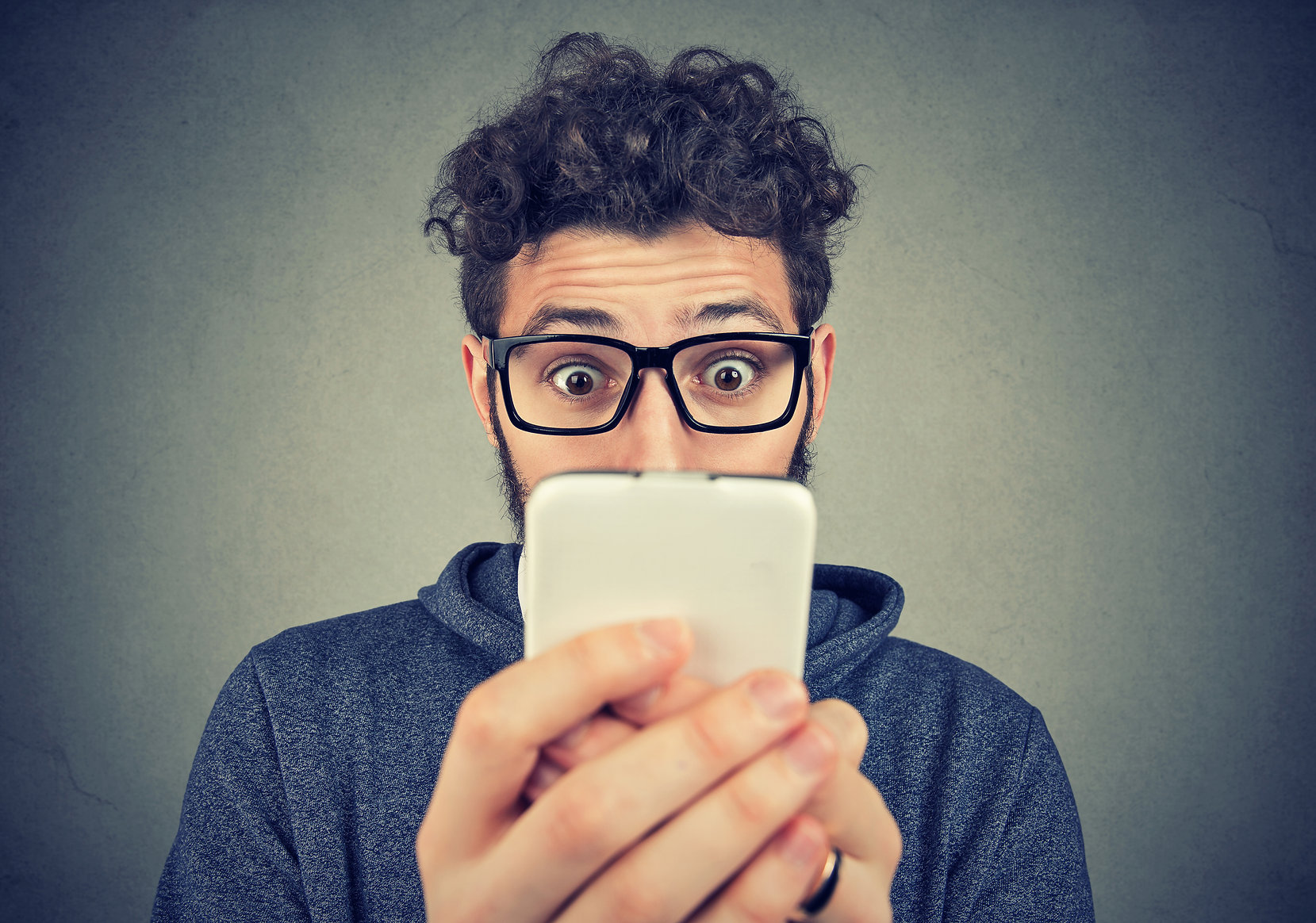 Canva - Shocked man watching smartphone.