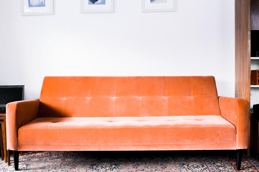 Foto eines orangen Sofas in einer Wohnung