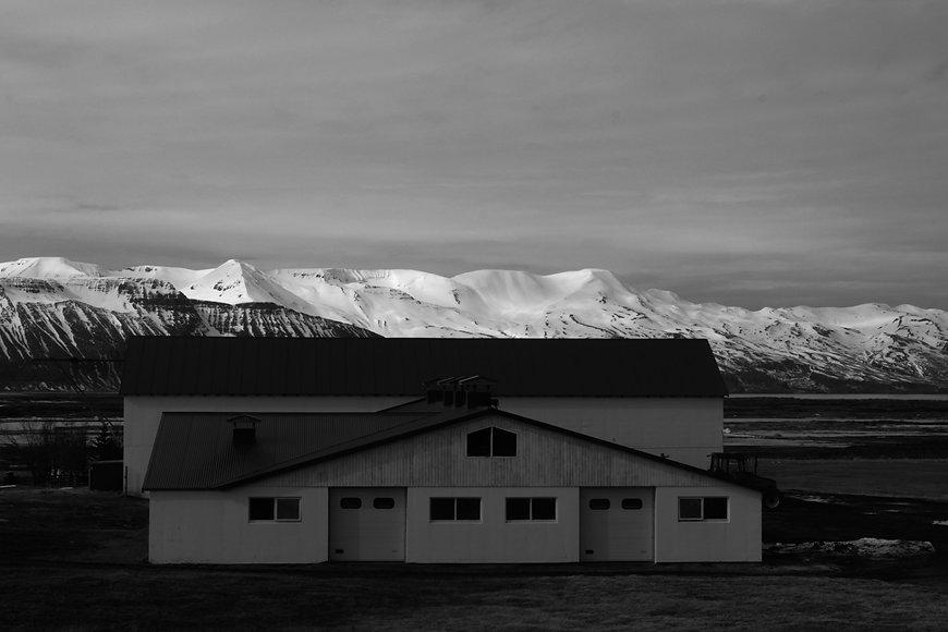 Schwarzweiss Foto eines Hauses mit Bergen im Hintergrund in Island