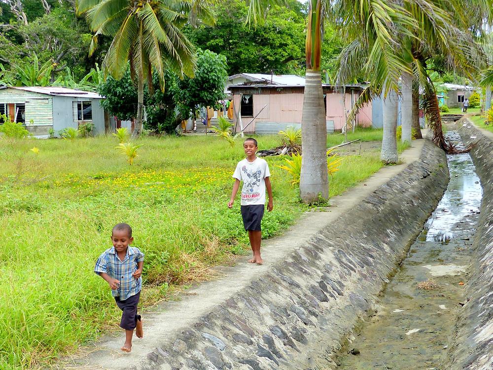 Des enfants jouent le long d'un canal de drainage à Kiuva.