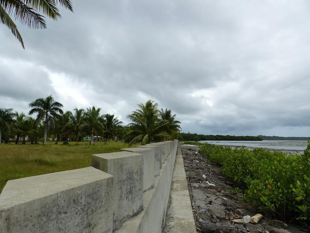 La digue de béton sépare la mer du village, Kiuva, Fidji.