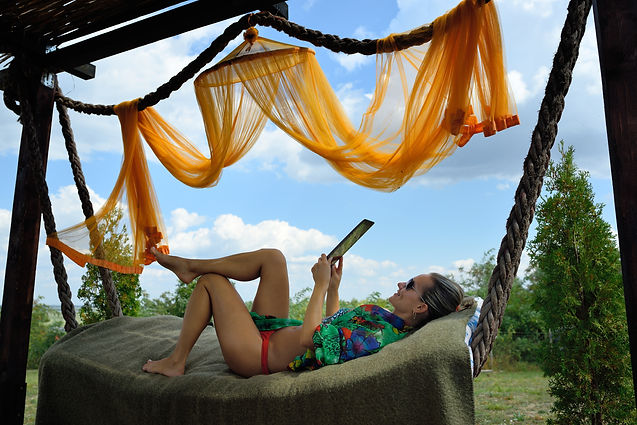 young woman relaxing in hammock with tab