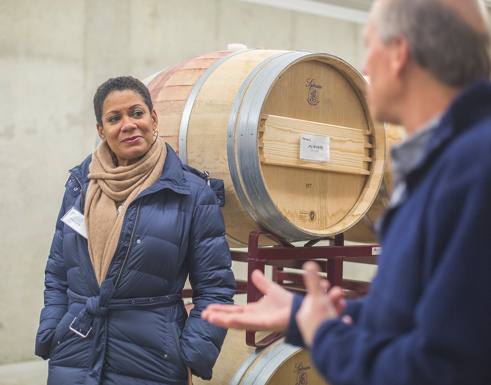 People at a vineyard talking about wine in front of barrels.