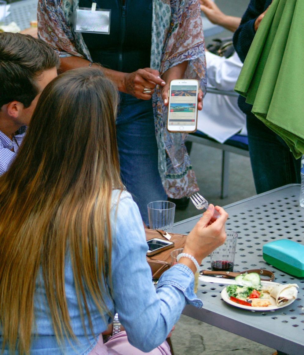People dining and looking at a mobile app demonstration.