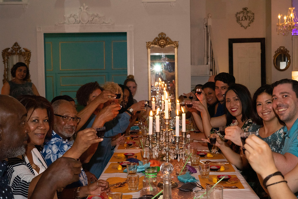 People toasting at a long dining table.