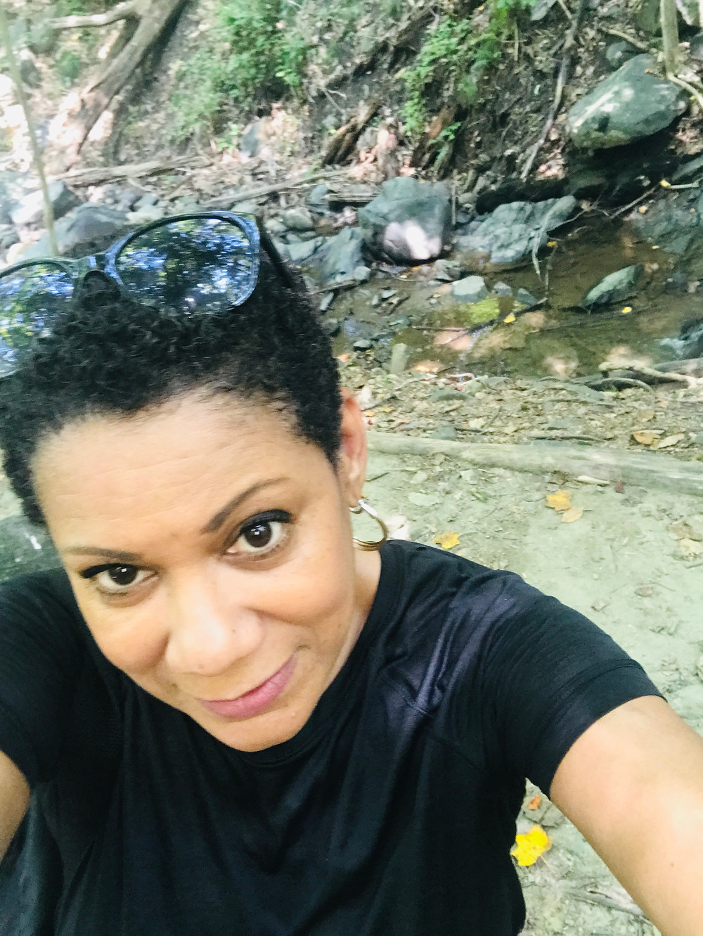 The author is hiking in park and posing in front of a creek.