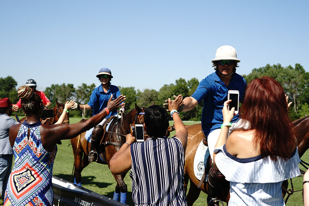 People shaking hands with polo players after a match.