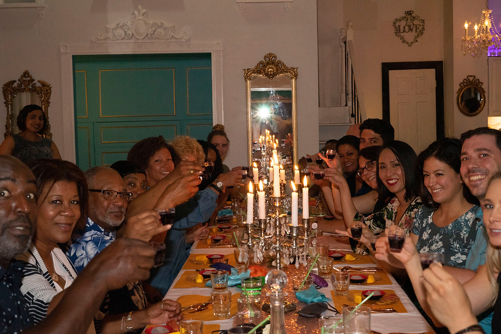 People toasting at a community table for a whiskey tasting and pairing.