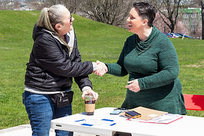 Mel, wearing a green sweater, shakes Shannon's hand from behind a table.