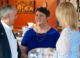 Mel, wear a blue shirt, sunglasses on her head, and a gold necklace, talks with two indivudals wearing dressy clothing.