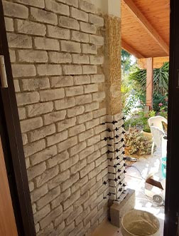 התקנת בריק לבן עם נגיעות שחור-אפרפר על קיר עם דבק