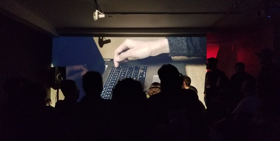 """An image showing the screening of Jay Afrisando's audiovisual work """"The (Real) Laptop Music :))"""" in front of audiences."""
