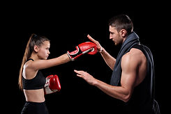 young-sportswoman-in-activewear-and-boxing-gloves-exercising-with-trainer-consulting-her-a