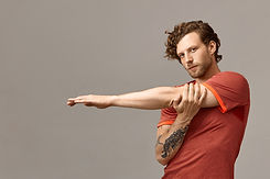 handsome-fashionable-unshaven-young-european-sportsman-with-tattoo-and-curly-ginger-hair-s