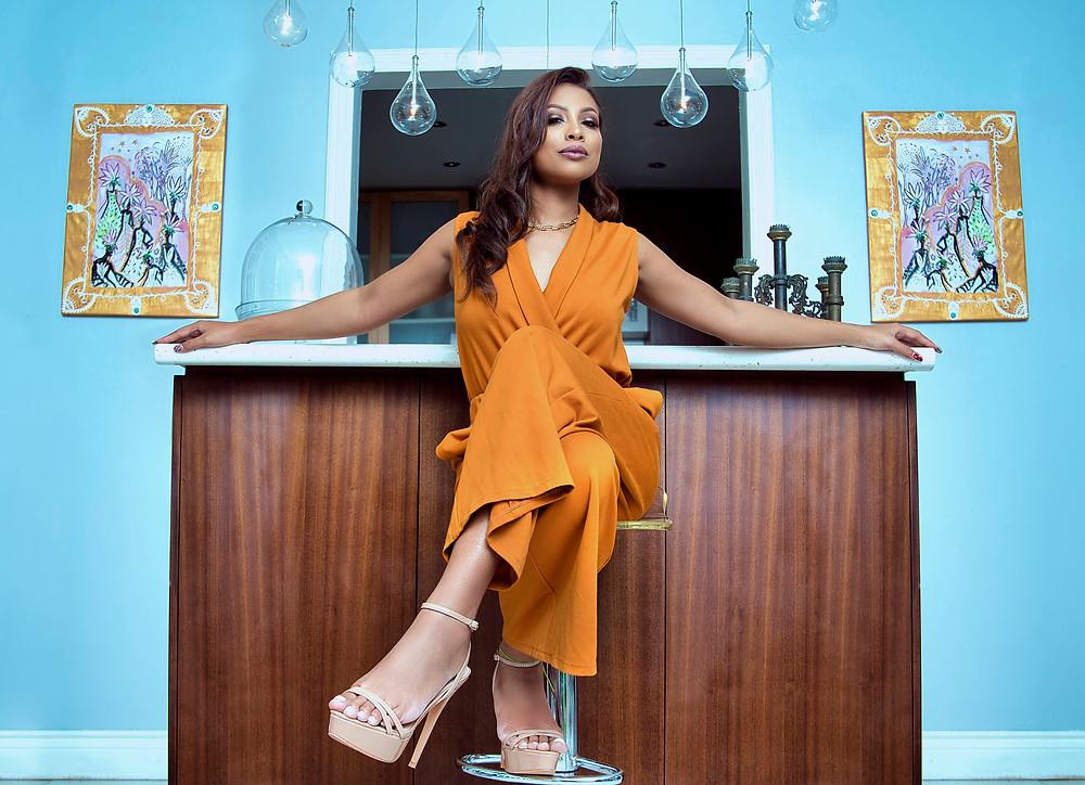 Model dressed in a burnt orange ankle length jumpsuit.