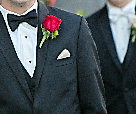 Groom's bout in a red rose. Groomens white rose with texture..jpg