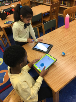 Fourth graders work with Sphero Mini robots in the library during Robotics Club