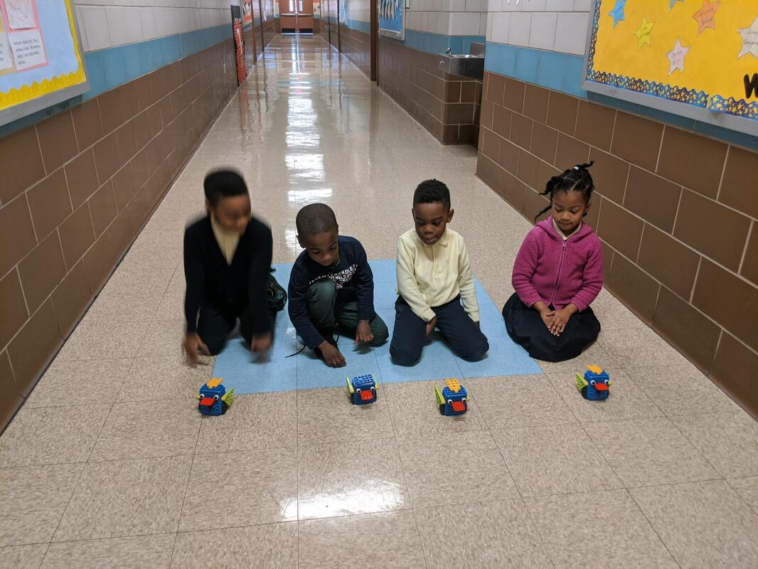 Ms. Garcia's kindergartners run their Robotis models in hallway