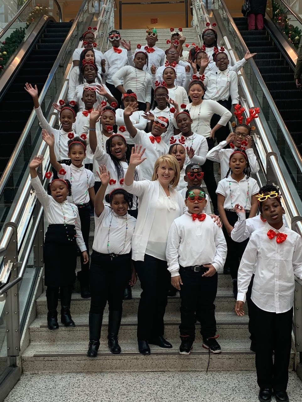 Ms. Grechko with chorus on an escalator at Kings Plaza mall
