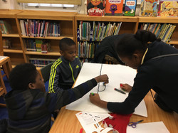 Students in grades 3 to 5 code Ozobots in the library
