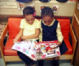 two girls read a magazine together