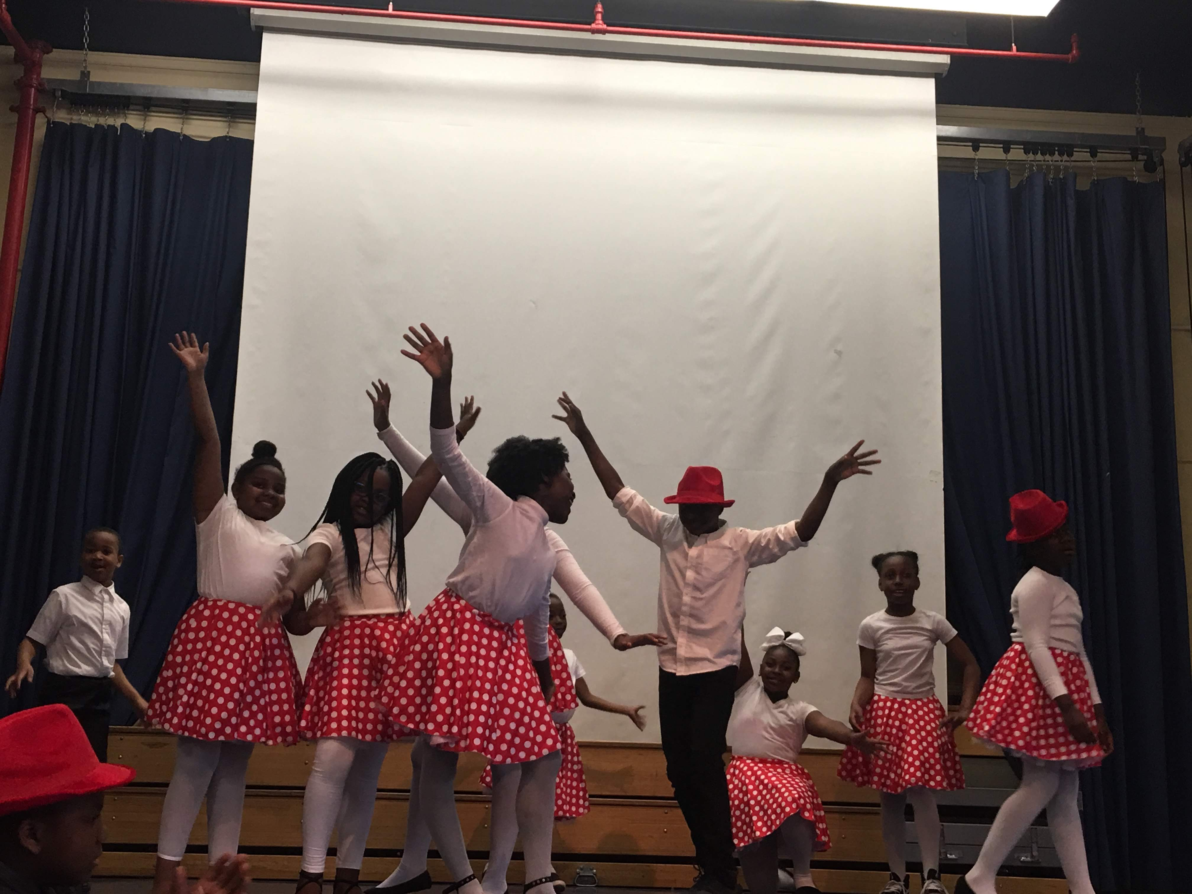 3rd, 4th, and 5th graders dance exuberantly on stage