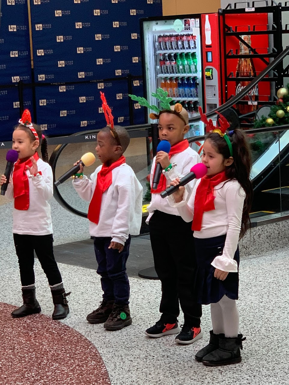 Four kindergartners sing