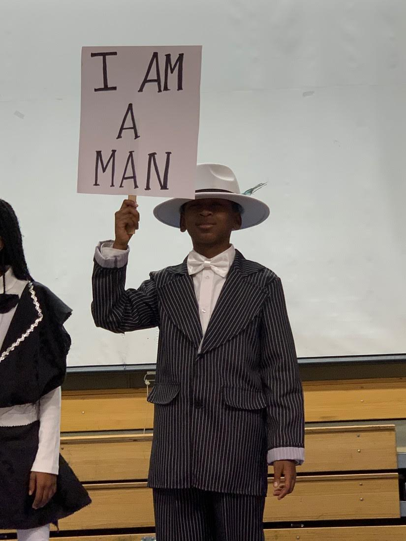 Ahmad in 1920's costume holds sign saying I Am A Man