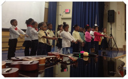 Kindergartners perform on stage with guitars and piano in foreground