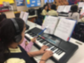 Students reading music and playing keybo
