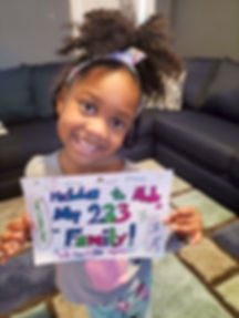 Girl holds sign saying Hello to All My 233 Family!