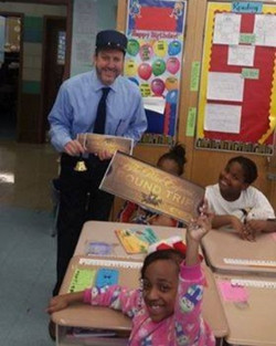 Mr. Goldberg dressed as conductor delivers tickets to Polar Express