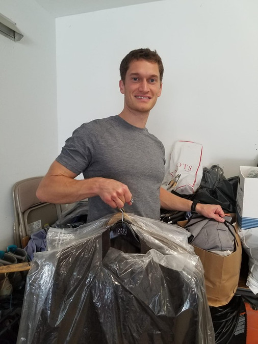 Holding some of the clothes from our first clothing drive.
