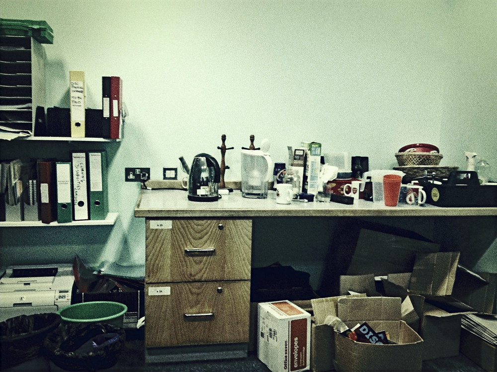 desk cluttered with folders, kettle, mugs etc. Boxes under the desk