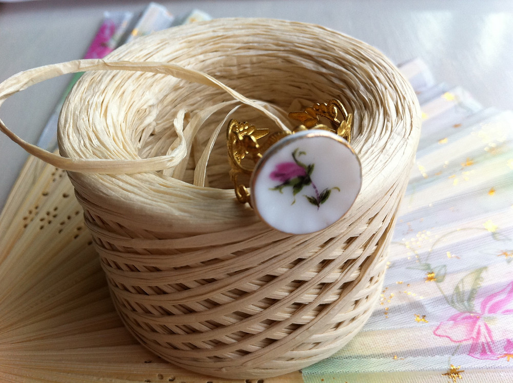 spool of raffia string with a decorative rose button attached
