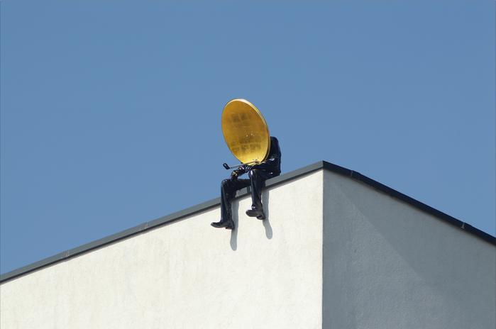 L'homme qui tend une parabole vers le ciel