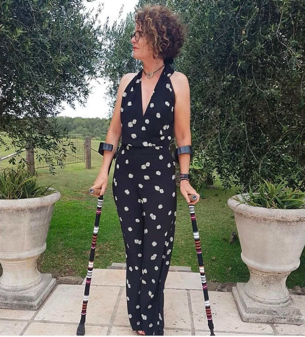 This image is a women standing in a garden patio wearing a black and floral designed jumper and using her Wide Stripes Forearm Crutch Skins available at PattiandRicky.com