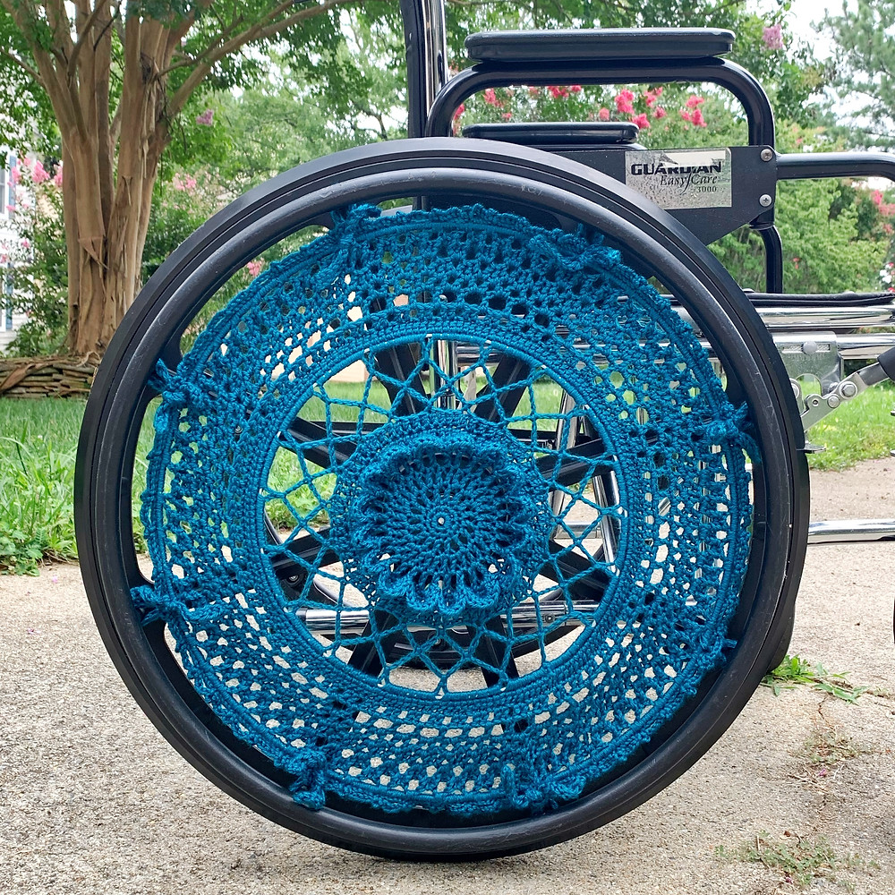 Close-up image of manual wheelchair, with a beautiful teal crocheted wheelchair wheel cover.