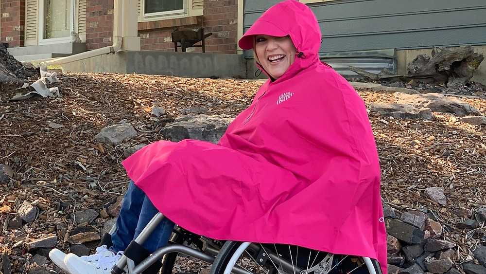 Kate is rocking the Rover Rain Cape in Minster Pink and has the hood up. She is doing tricks with her wheelchair.