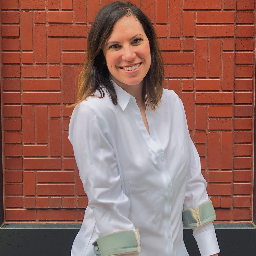 This is an image of Molly wearing her white, Smart Adaptive shirt, available at PattiandRicky.com. Molly is a white female with brown hair a little past her shoulders. She is standing in front of a red brick building, looking directly at the camera and smiling. You would never know this shirt is actually Velcro. Molly is using her forearm crutches.