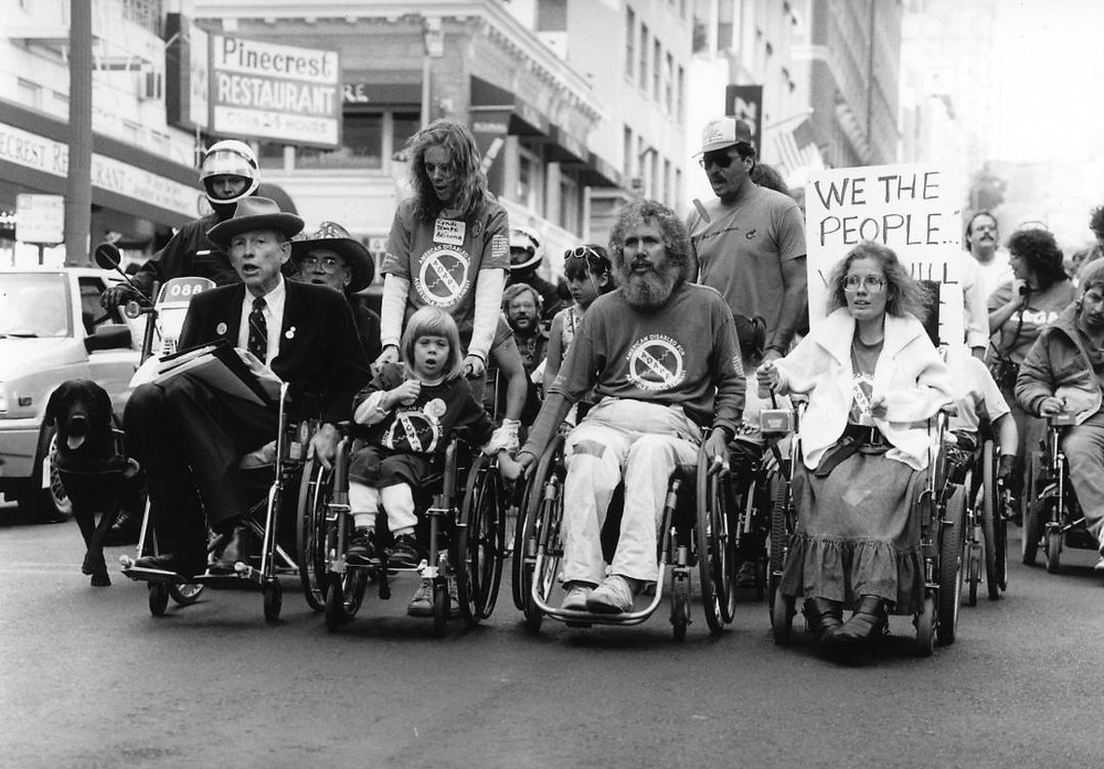 This is a black and white photograph of ADAPT activists, including Jennifer and her mother Cynthia, protest the inaccessibility of public transportation in San Francisco, CA in 1987. This is a photograph individuals with and without disabilities marching for access. Pictured from left: Justin Dart Jr., Jennifer Keelan-Chaffins, and her mother Cynthia Keelan, Bob Kafka, and Dianne Coleman.