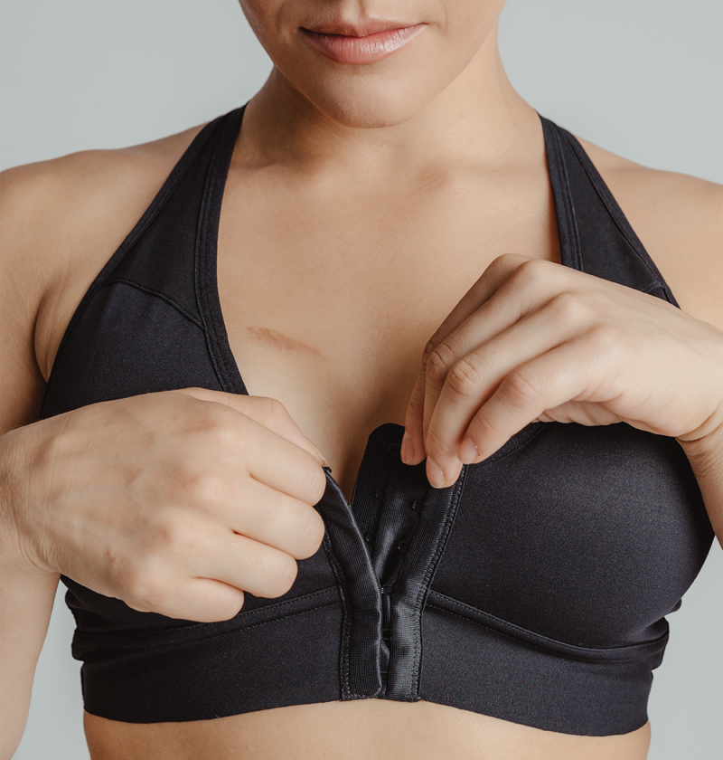 Close up image of the Bianca bra showing the hook-and-eye front closures and the model is opening up the top hook-and-eye closures