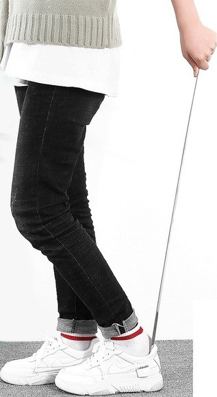 This is a zoomed in image of a white, female model using a long shoehorn to put on or off her white Nike sneakers. She is wearing black jeans and a white shirt with a gray sweater over it. She is able to stay standing while using the long reach shoehorn.