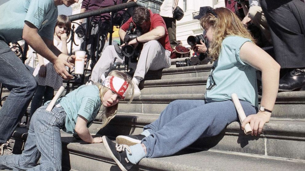 "This is a colored photograph of Jennifer Keelan-Chaffins at the age of 8 years old, climbing up the steps of the U.S Capitol, the ""Capital Crawl"". She is on her hands and knees climbing.She is wearing an ADAPT bandana as a headband which is white with red letters, light blue jeans, and a t-shirt. She is a cute white little girl with blonde hair. She is climbing and looking directly at the camera."