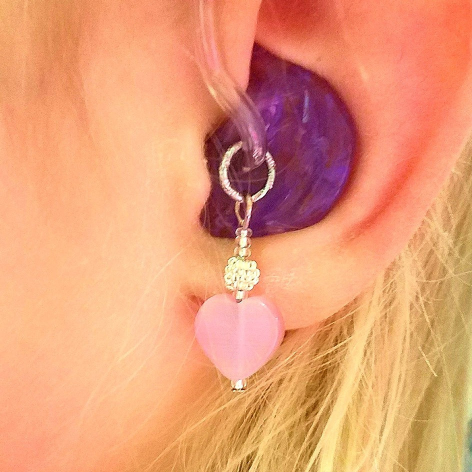 Pink heart hearing aid charm with silvertone accents.