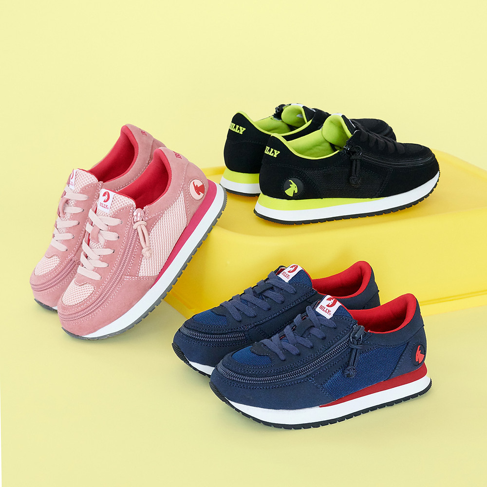 Three pairs of Billy Footwear kids shoes that zipper around foot making them easy-on/easy-off. There is a pink and red pair, black and green pair, and navy blue and red pair.