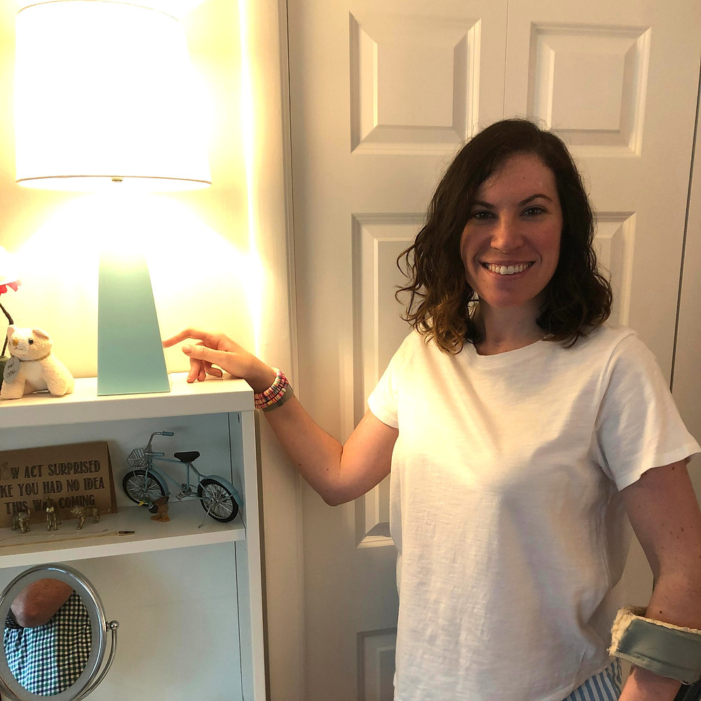 This is another image of Molly touching her touch lamps to turn them on. She is smiling and looking directly at the camera. She is wearing a white t-shirt.