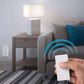 This is an zoomed in image of a white, male model using a white remote to turn on and off his lamp that is nearby on a side table, next to a couch. You can see that the lamp has been plugged into a remote controlled outlet that is plugged into the outlet, allowing the lamp to turn on when using the remote.