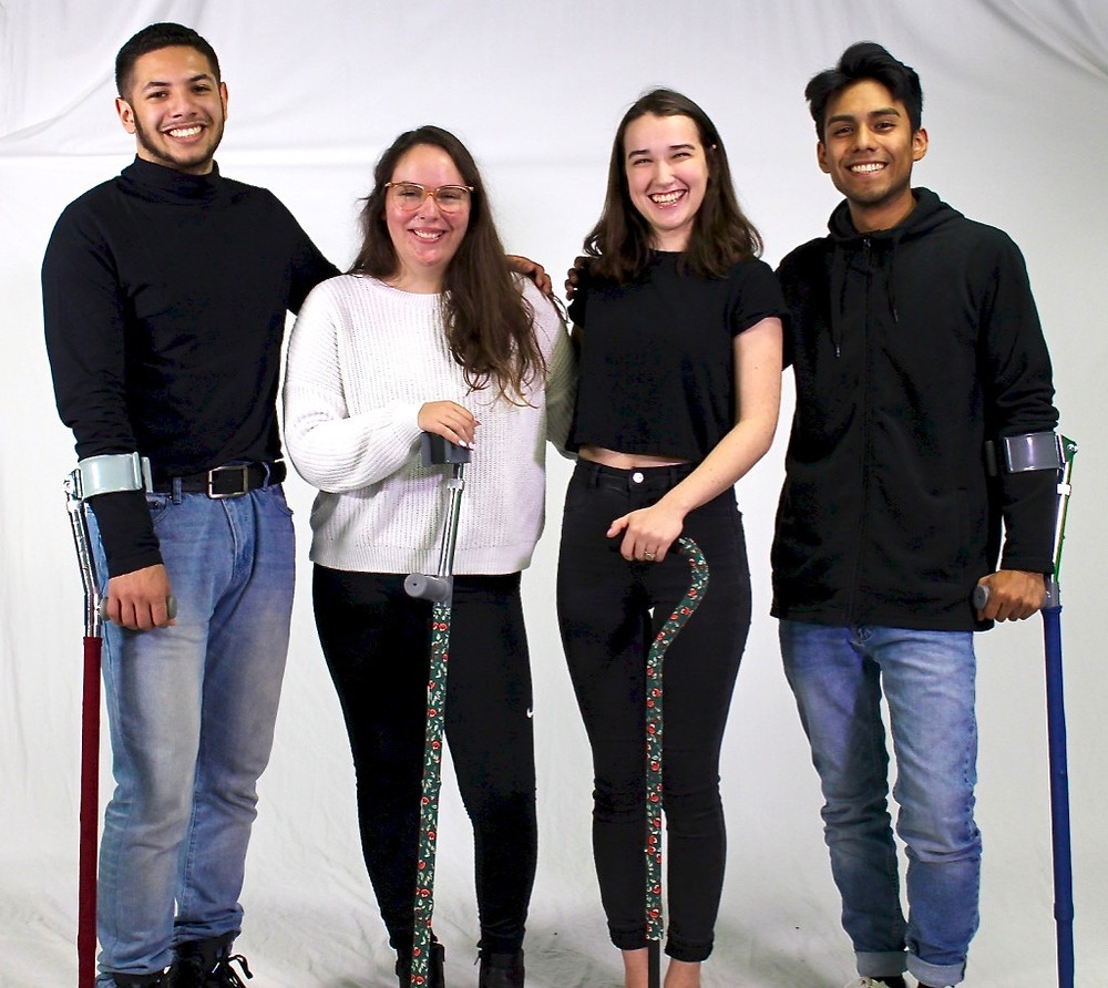 This image is of four models (2 men and 2 women) all have a forearm crutch except one women who has a cane. The male models have solid blue and solid red forearm crutch skins and the women models both have green and red floral skins. They are all smiling and looking directly at the camera.