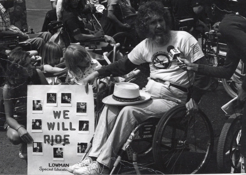 "This is a black and white photograph. On the left is Jennifer's mom Cynthia crouching down next to Jennifer, who is in her wheelchair. Next to Jennifer is activist, Bob Kafka. Bob is a white man with curly hair, mustache, and long beard. He uses a wheelchair. Cynthia, Jennifer, and Bob are all holding a poster that says ""We Will Ride"" and has photographs that are not visible on it. Bob is getting interviewed by a reporter."